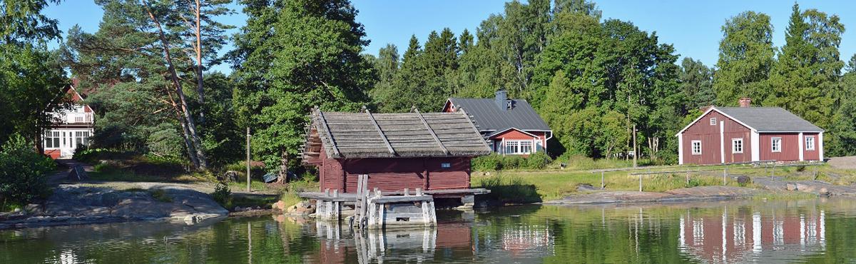 Punaisia puisia museo rakennuksia rannalla.