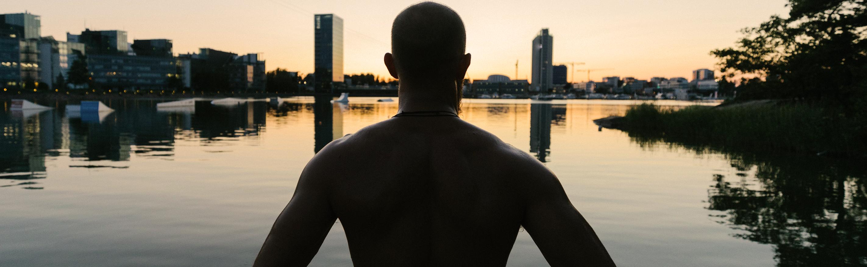 Mies selin katselemassa auringonlaskua Keilaniemen rannalla. Horisontissa näkyy korkeita rakennuksia.