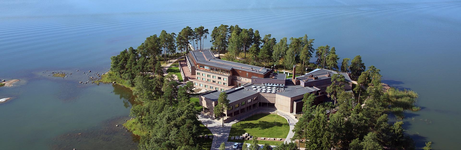 Hotelli rakennus ilmasta käsin kuvattuna. Rakennusta ympäröi puut ja meri.