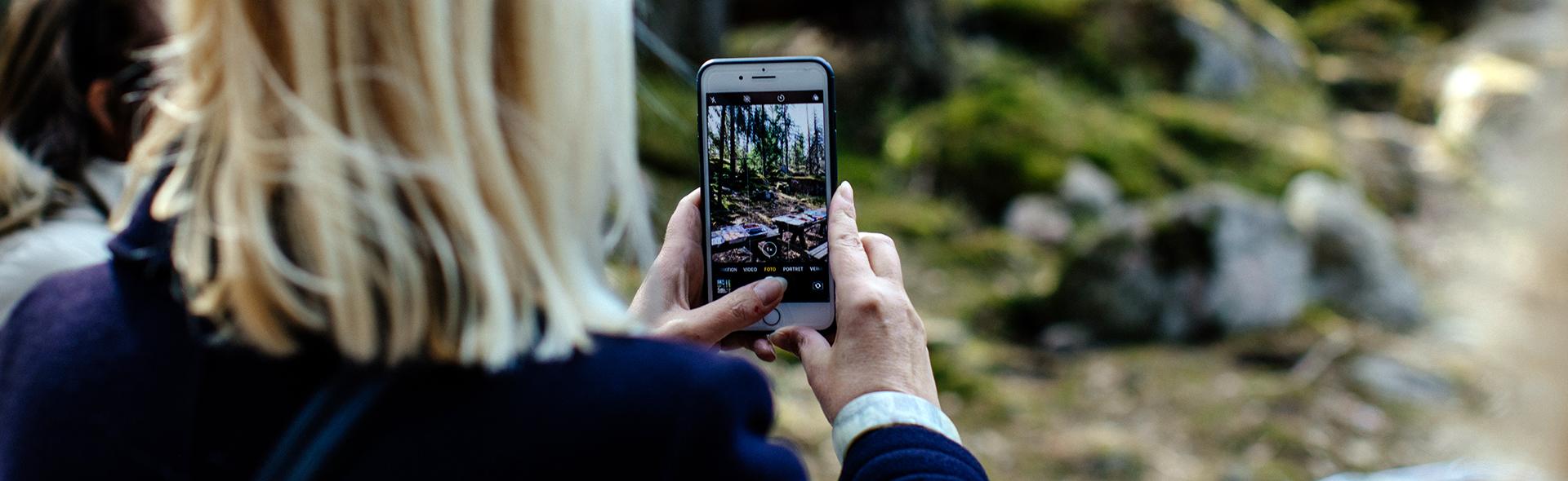 Nainen kuvaa kännykällä metsämaisemaa.