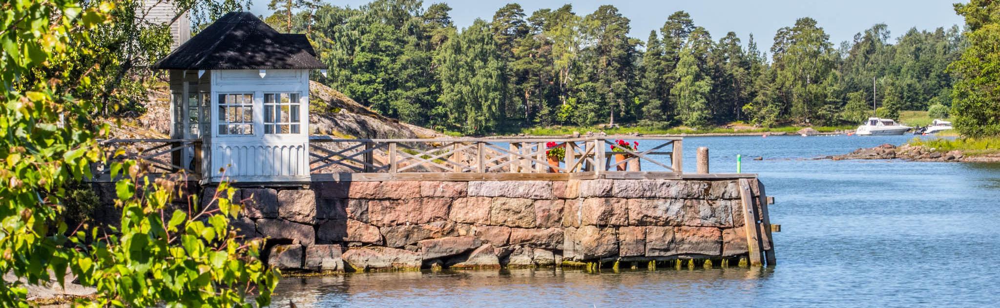 En liten brygga vid havet i den sommarliga och solskinnande Esbo skärgård.
