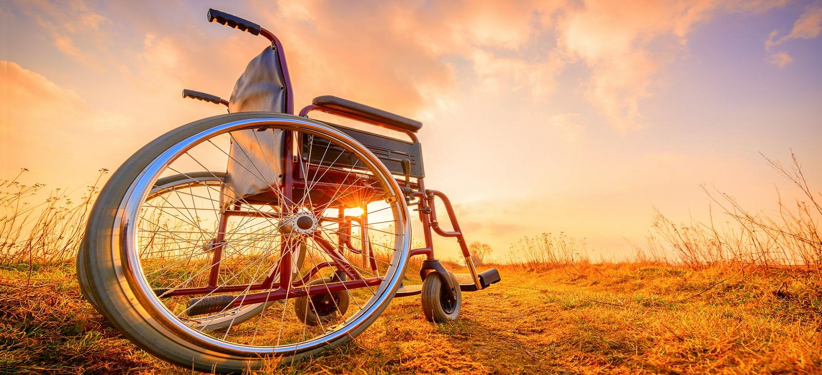 Tyhjä pyörätuoli pellon laidalla aurongon laskiessa.