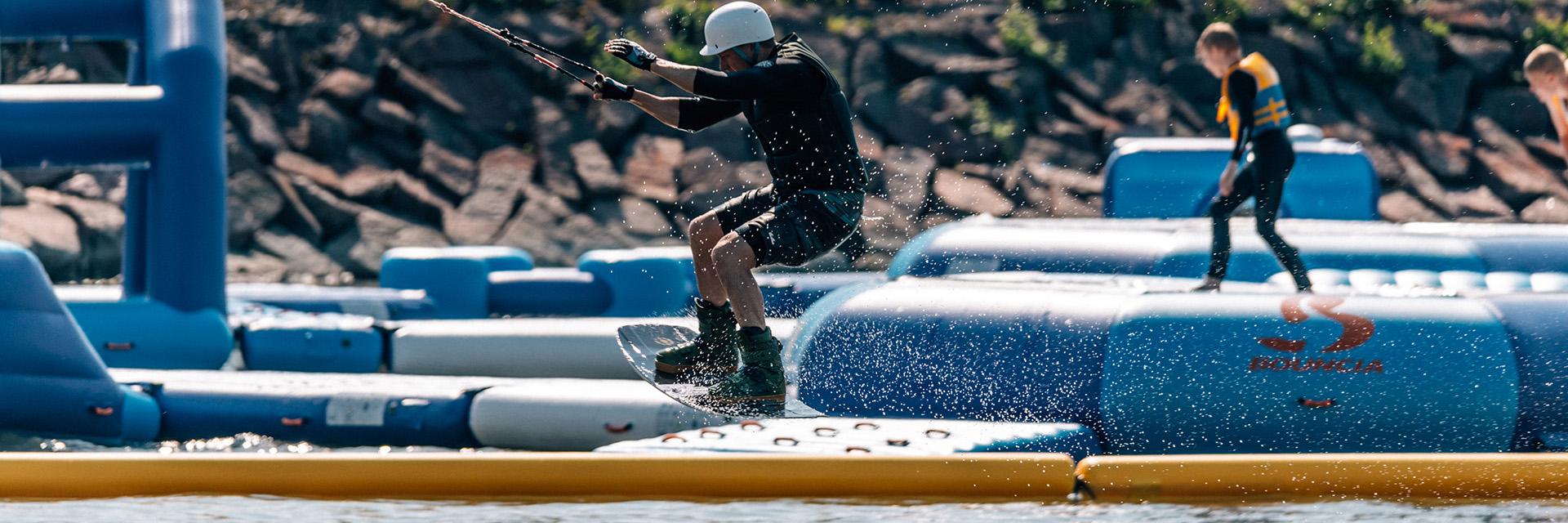 Mies wake boardaamassa Laguunilla kelluva vesipuisto taustalla