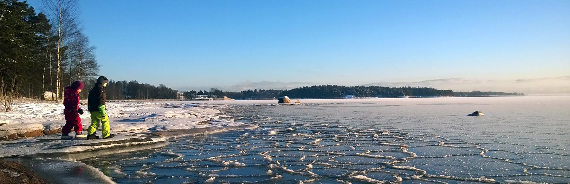 Kaksi lasta kävelee jäätyneen meren rannalla.