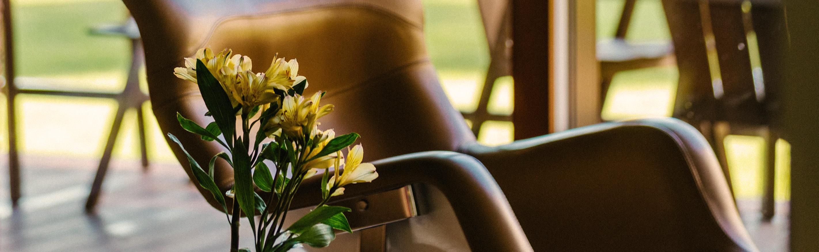Hotellin yleisissä tiloissa oleva design-nojatuoli ja kukkia maljakossa pöydällä.
