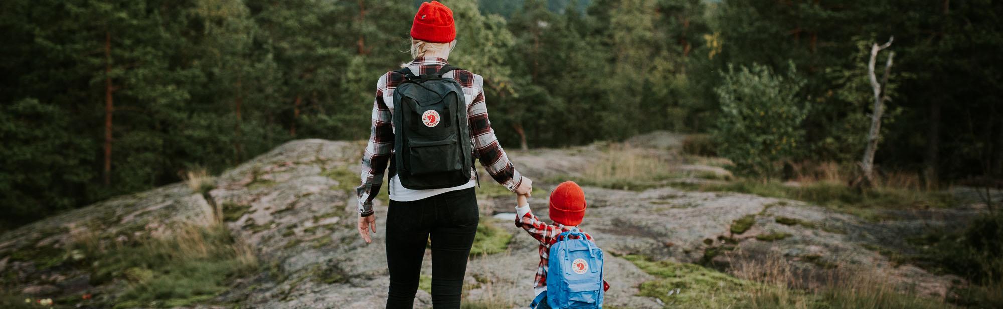 Äiti ja lapsi retkeilevät kallioisessa metsämaastossa.
