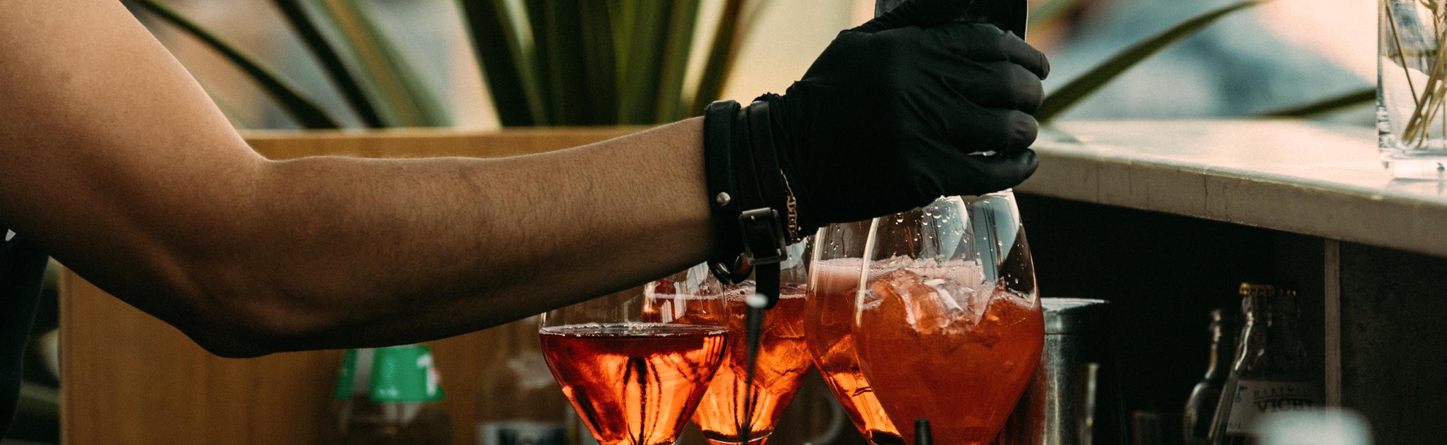 Tarjoilija valmistaa baarissa tai terassilla cocktailia lasiin.