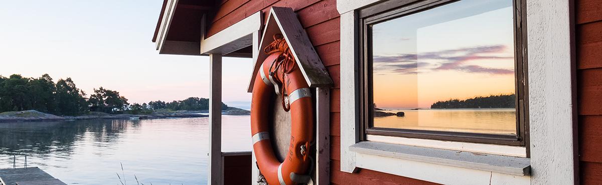 Puinen saunarakennus meren rannalla. Ikkunasta heijastuu meri ja laskeva aurinko.