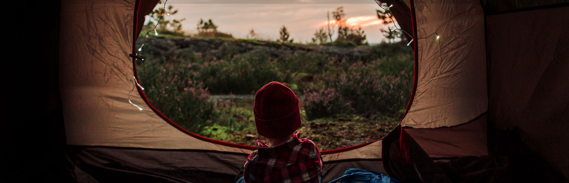 A child sitting in a tent watching the sun setting behind the forest.
