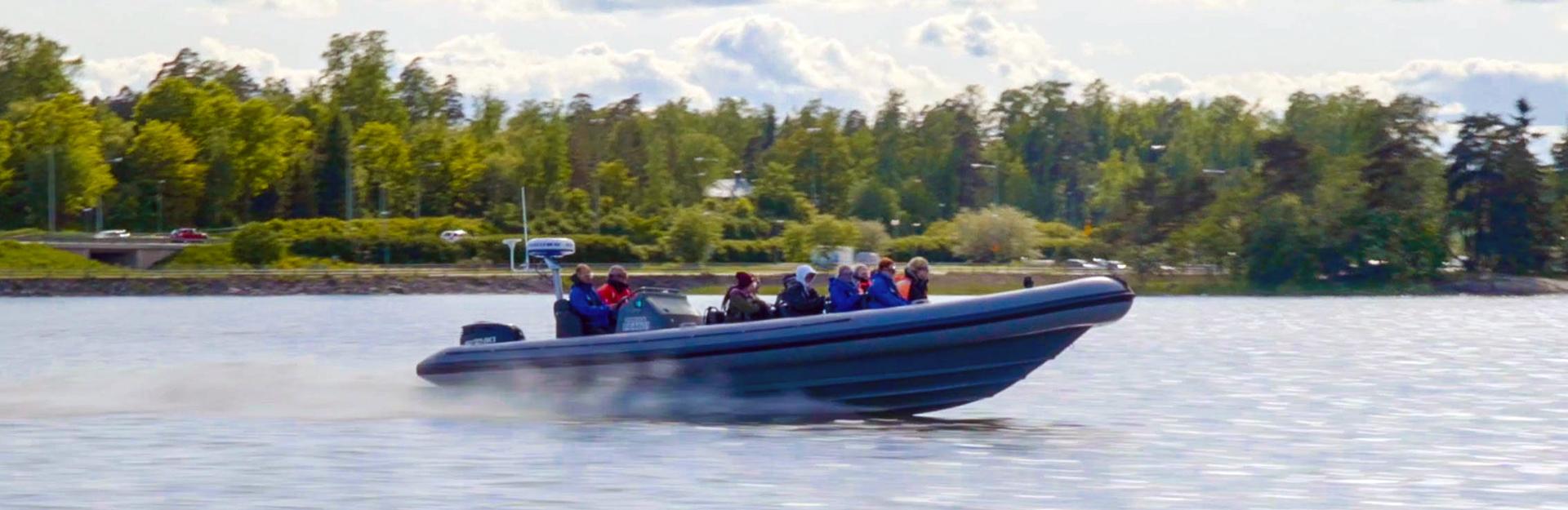 Ryhmä ihmisiä rib-veneen kyydissä.