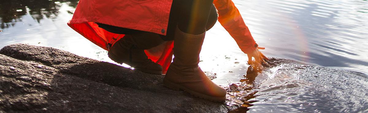 Naisen käsi kurottaa metsälammen veden pintaan.