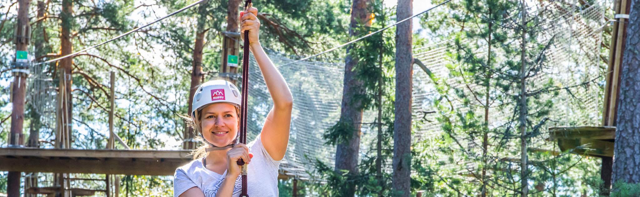 Nainen liukuu ilmassa kiipeilypuiston valjaissa.