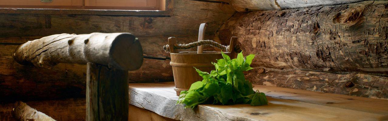 Kuva saunan lauteilta, jossa on saunakiulu ja vihta.