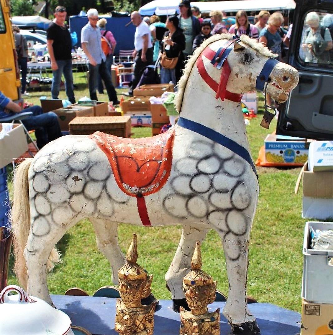 En leksakhäst som står på marken på loppmarknaden på en sommardag.