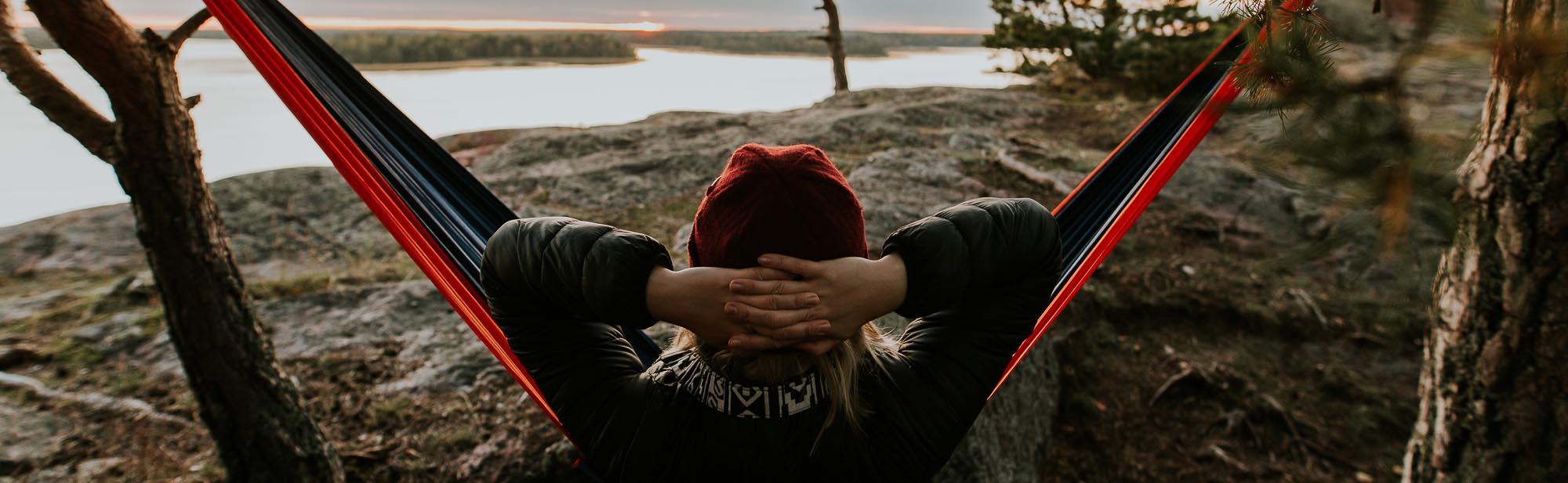 En person ligger avslappnad i en hängmatta på en stenig strand vid havet och tittar mot havet.