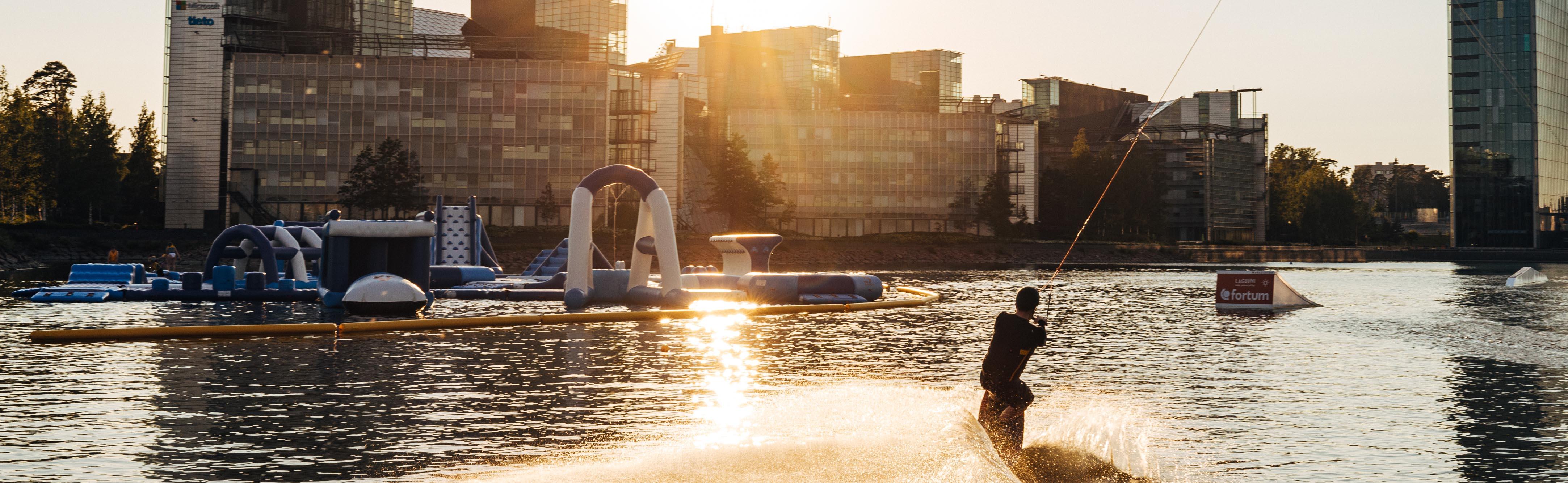 Henkilö wakeboardaa merellä, Keilaniemen edustalla kesäiltana auringon laskiessa.