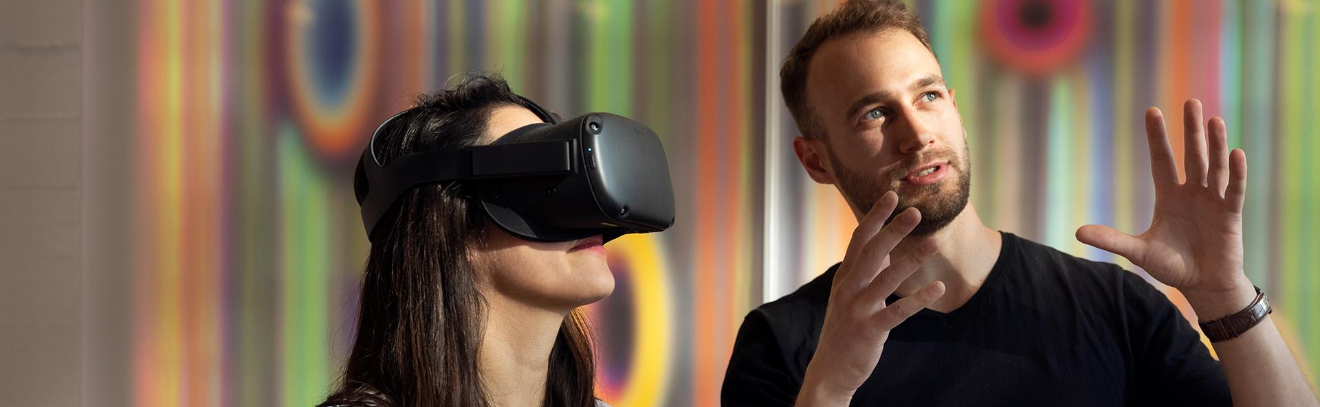 Nainen katselee VR-laseilla ja mies selostaa tapahtumia vieressä.